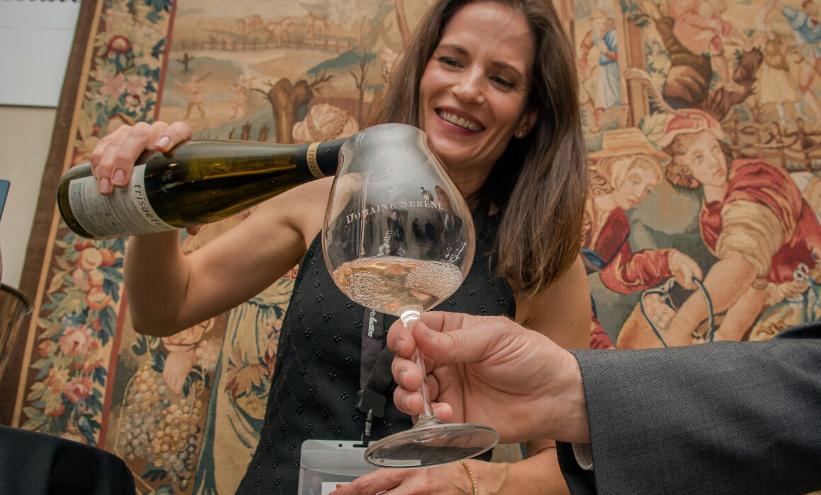 Woman pours white wine into Domaine Serene logo glass