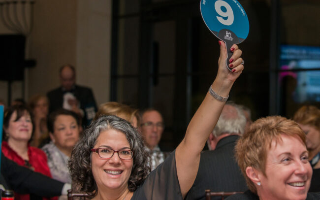 Auction attendee with her paddle raised.