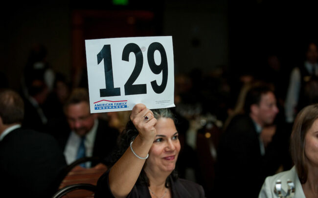 Auction attendee holding up her number