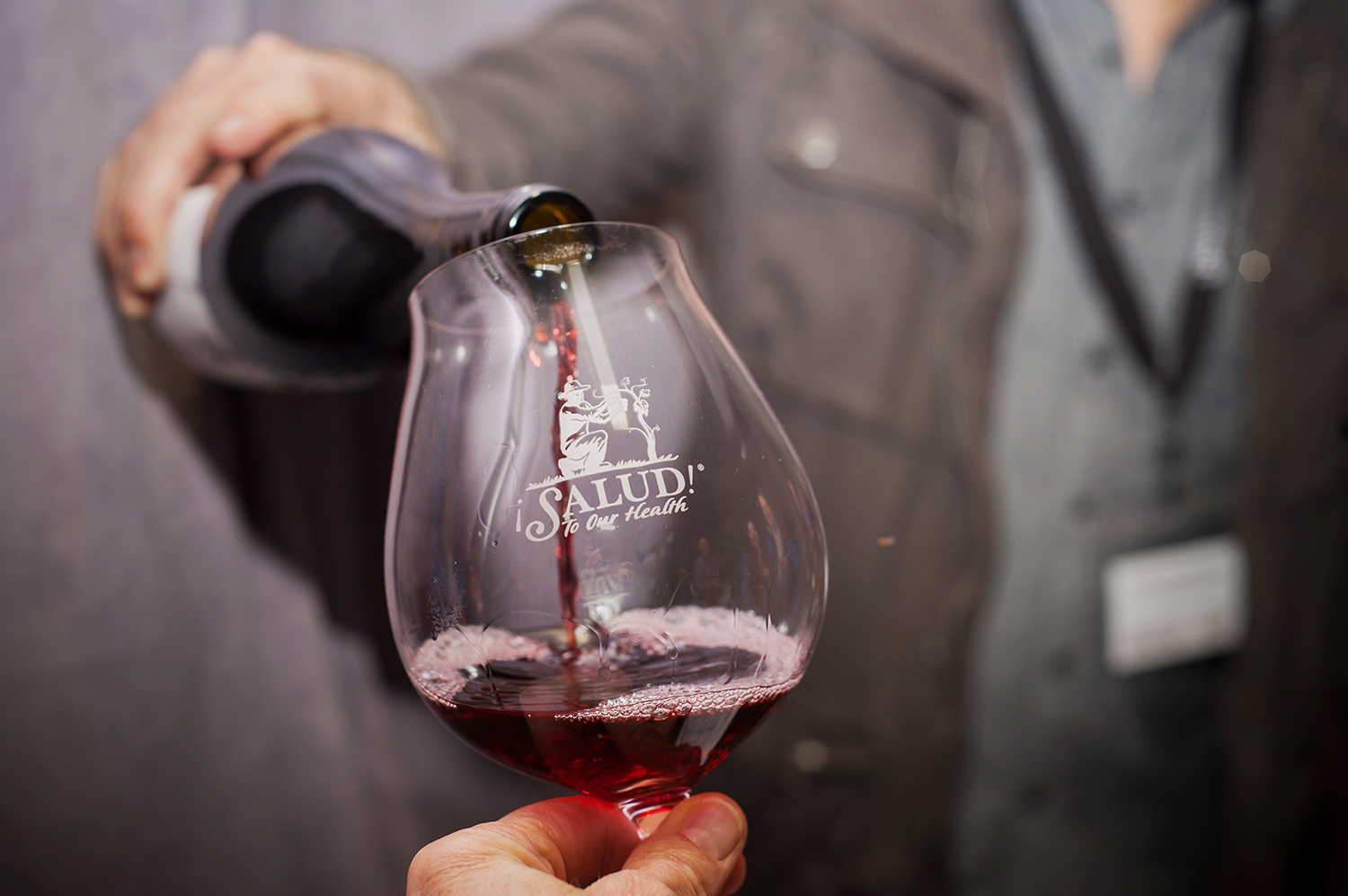 Wine being poured into a ¡Salud! logo glass