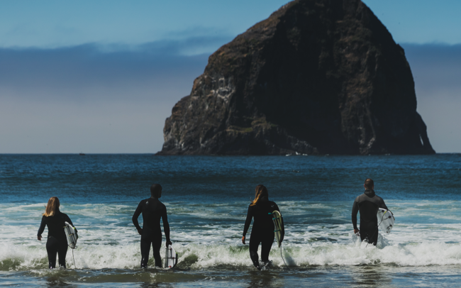 Four people walking into the ocean with surf boards