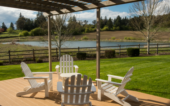 Patio with view of pond and white Adirondack chairs
