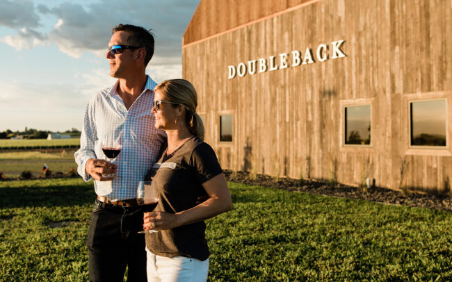 Doubleback winery with two people standing out front with wine glasses