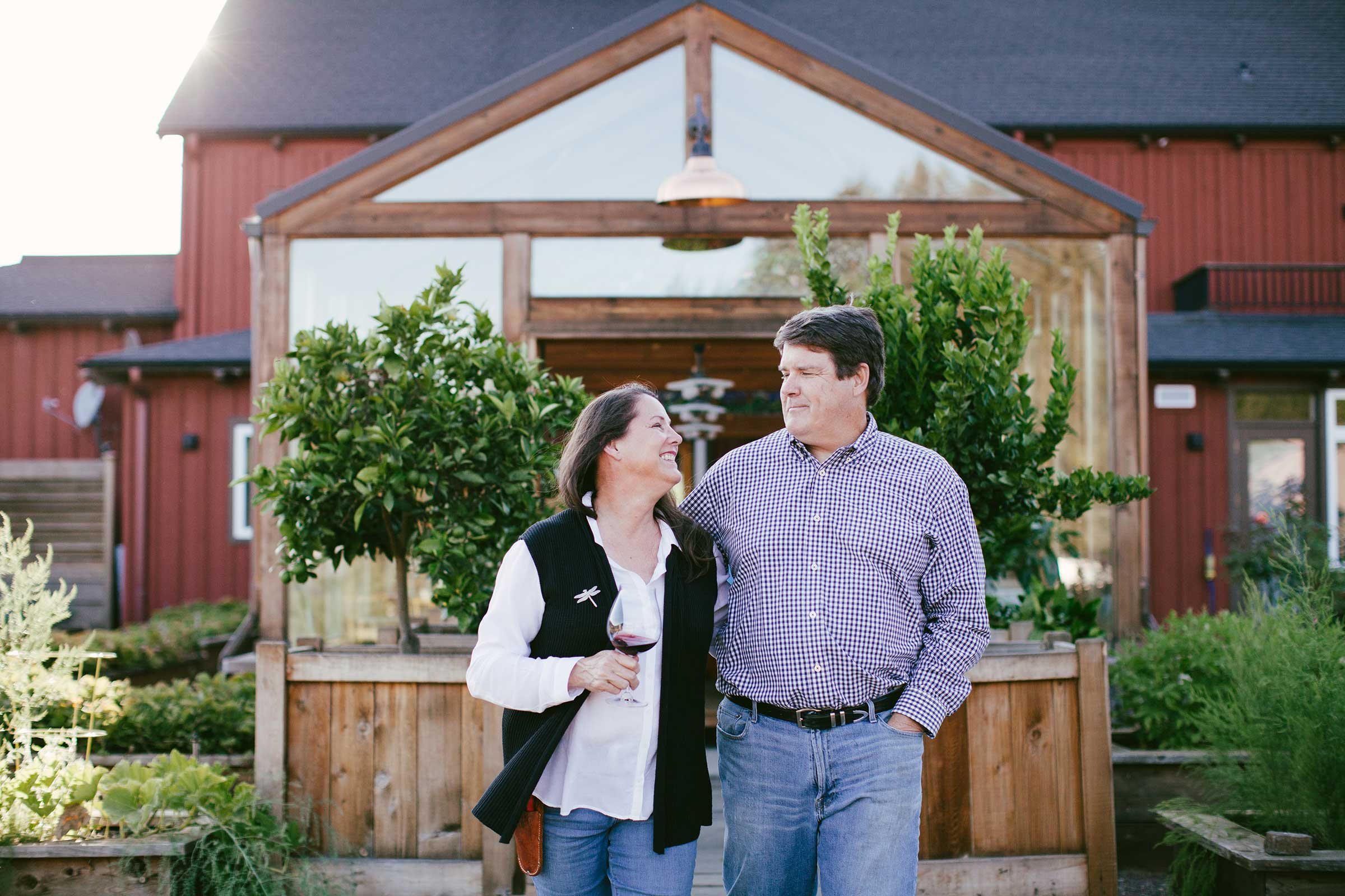 Two people standing in front of a red barn building