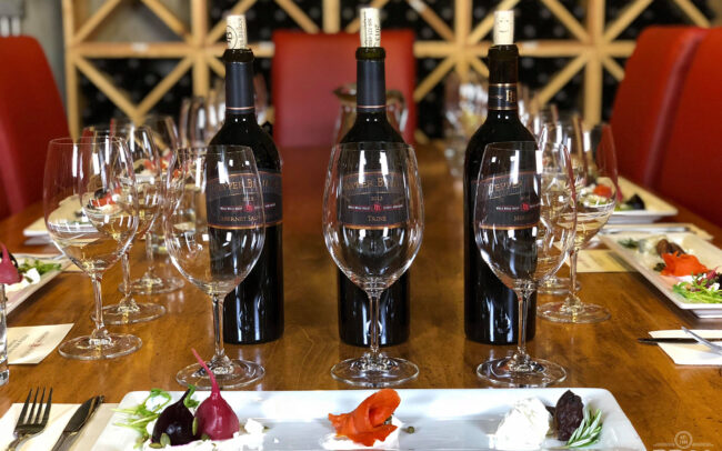 Three bottles of Pepper Bridge wine on a table with glasses and hors d'œuvres